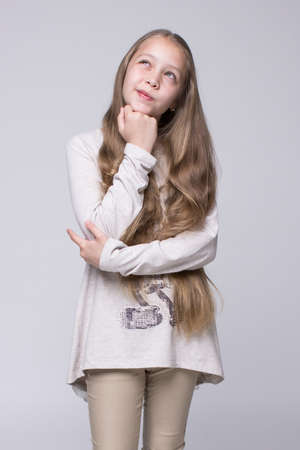 bewildered: portrait of bewildered teenage girl fashionably dressed standing on a gray background Stock Photo