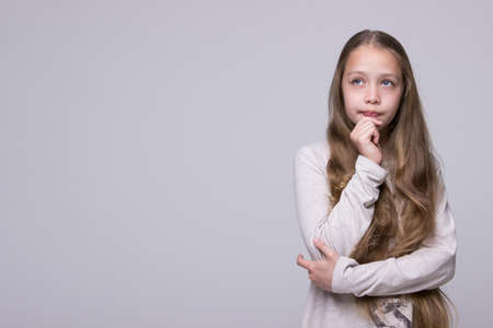 bewildered: portrait of bewildered teenage girl fashionably dressed standing on a gray background poster free space on the left