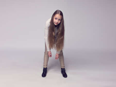 center position: funny teenage girl fashionably dressed standing on a gray background, poster center position