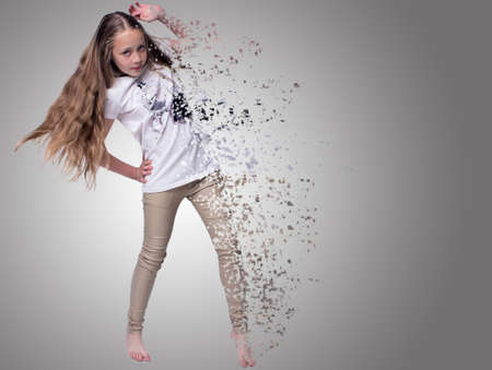 distort: portrait of teenage girl fashionably dressed standing on a gray background dance, effect distort Stock Photo