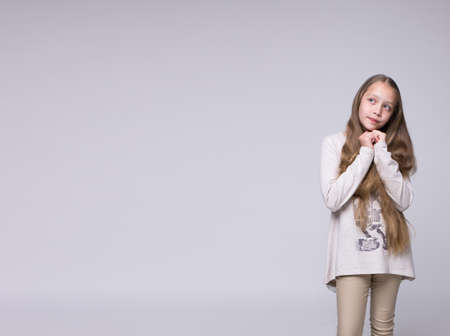 bewildered: portrait of bewildered teenage girl fashionably dressed standing on a gray background poster free space on the right