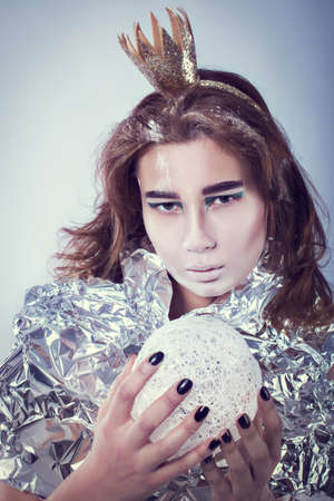 coronet: Portrait of pretty woman wrapped in foil with coronet looking forward standing on light grey background, vertical picture Stock Photo