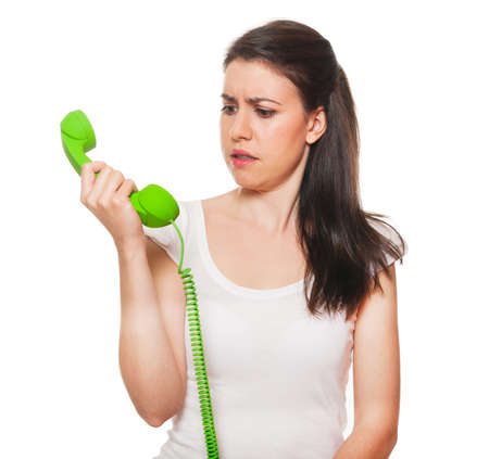 Young female getting stressed by someone on the phone. Isolated on white. photo