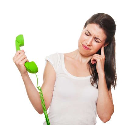 Young female getting stressed by someone on the phone. Isolated on white.