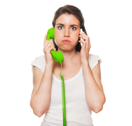 annoying: Young female getting stressed by someone on the phone. Isolated on white.