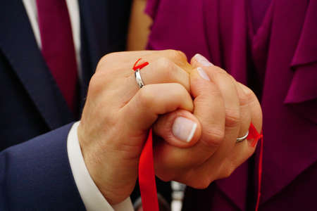 Newly engaged couple hands with ribbon close up view