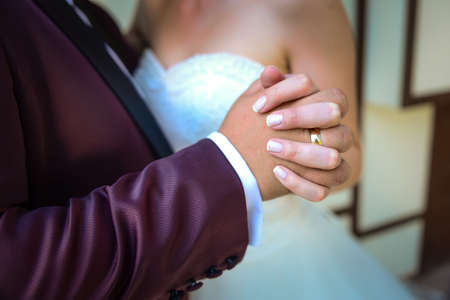Bride and groom holding hands with engagement rings on their fingers close up view wedding shoot concept Imagens