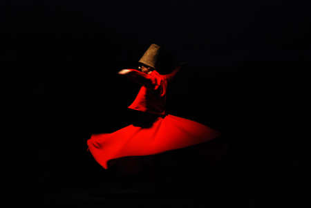 Whirling dervish on black background in red costume