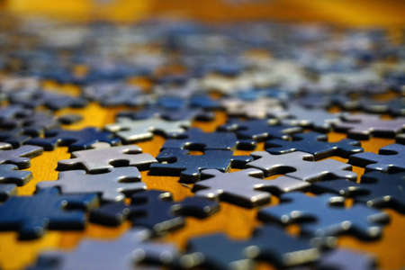 Making puzzle at home on wooden background bokeh effect close up view