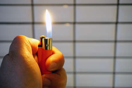 Burning lighter in man hand copy space at side