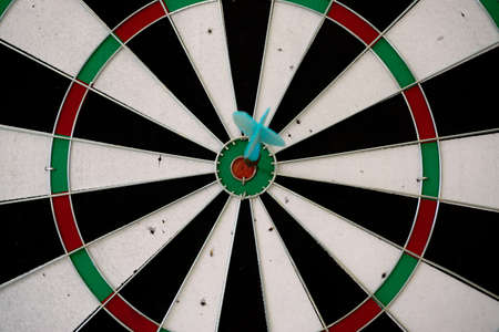 Dart game with the arrow on the center target close up view