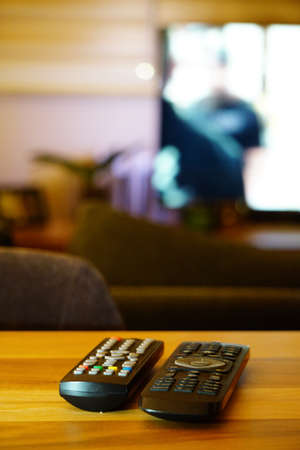Two television remote controllers on wooden background image with shallow depth of field Stock Photo