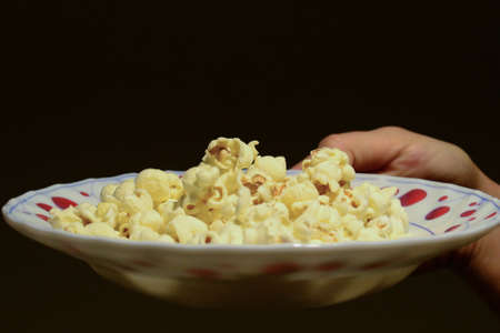 Popcorn in  the dish in woman hand close up view