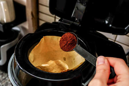 Filter coffee on the spoon to poured into the machine in the morning Archivio Fotografico