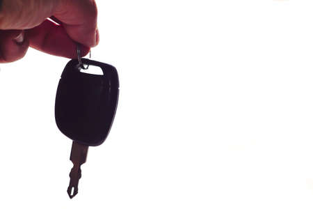 Car key in man hand close up view on isolated background