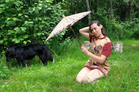 herrin: schwarzer Hund mit seiner schönen Herrin gekleidet in einem Mini-chinesischen Kleid mit einem Sonnenschirm in der Hand Lizenzfreie Bilder