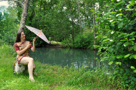 mini umbrella: Beautiful young woman with a parasol, sitting in the wilderness waterfront