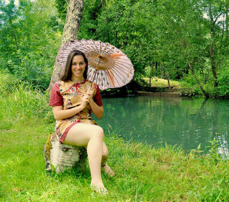mini umbrella: beautiful young woman in a Chinese robe sitting on a tree trunk with an umbrella