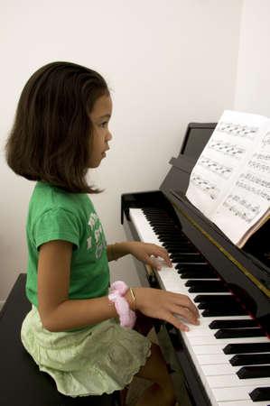tocando el piano: Asia chica tocando el piano Foto de archivo