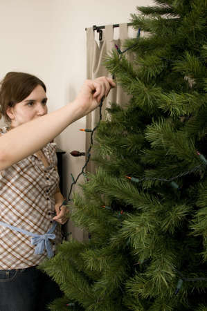 artificial lights: Woman Putting Lights on Tree
