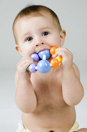 Cute Baby Chewing on Toy Imagens - 8190992