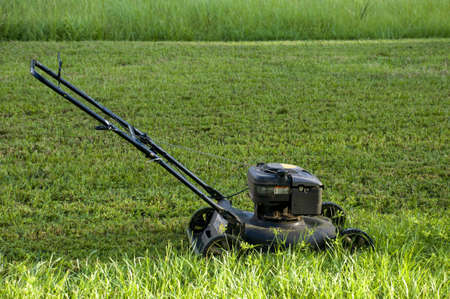 lawn mower: Lawnmower on Grass Stock Photo