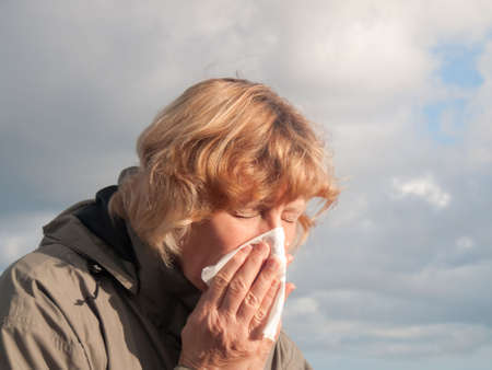 hayfever: Mature woman sneezing into tissue