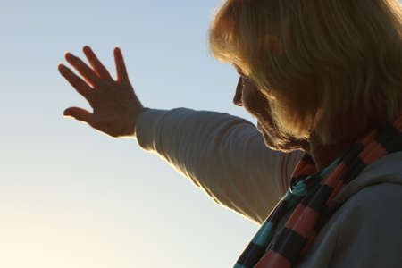 stretched out: Mature woman reaching out to the sun Stock Photo