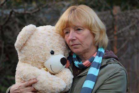 companionship: Mujer madura triste que abraza el oso de peluche Foto de archivo
