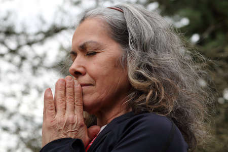 clasped: Mature woman praying with hands clasped Stock Photo