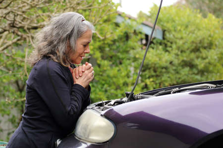 Mature woman praying over her car for safety and guidance