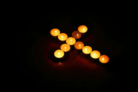 easter cross: The sign of the cross in the dark made by candles.