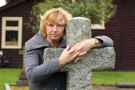 Mature woman praying with hands clasped over a stone cemetery cross, with church in background. Stock Photo
