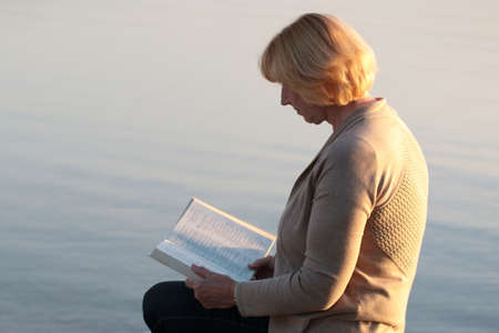 the scriptures: Senior adult woman reading Bible at the beach