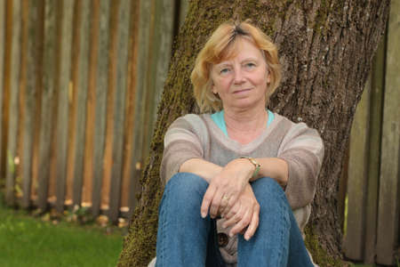 destress: Mature woman resting against tree Stock Photo