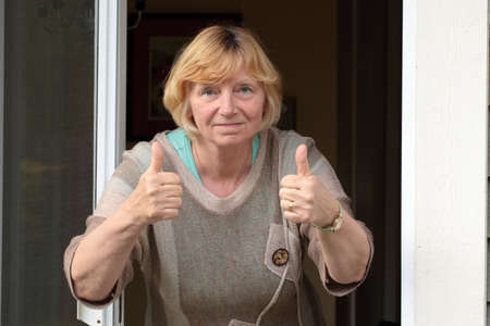 two thumbs up: Two thumbs up mature woman leaning out back door.