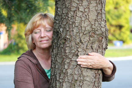 arm around: Mature woman with arm around tree trunk. Environmental concept. Stock Photo