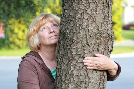 looking up: Mature woman arm around tree looking up. Mental healthpeaceenvironment concept. Stock Photo