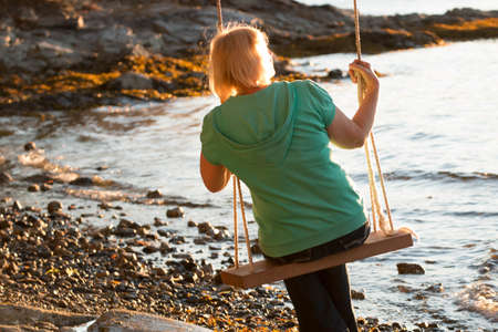 mature woman sitting: A mature woman sitting on a swing and looking out at the sunset and ocean.