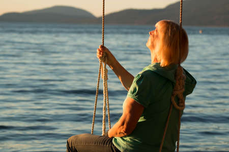 A mature woman leaning against a swing's ropes while looking out at the ocean and sunset.