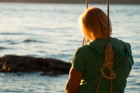 mature woman sitting: The back of a mature woman sitting on a swing while looking out at the ocean and sunset. Stock Photo