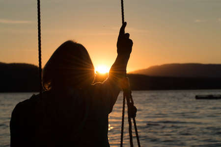 oudoors: Mature woman on swing at sunset