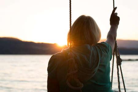 oudoors: Mature woman facing sunset on beach