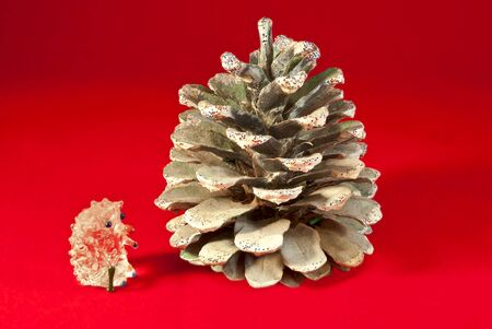 Quartz hedgehog near the fir-cones, isolated on a red background