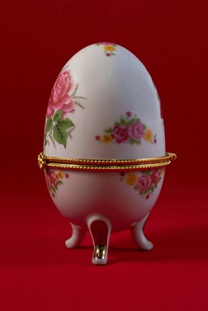 The box in the form of porcelain eggs with a painting, on a red background