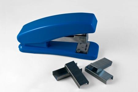Blue stapler and staples on a light background