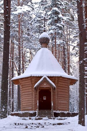 Wooden chapel in winter forest;