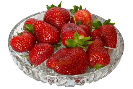 The berries are juicy strawberries in the crystal plate isolated on a white background