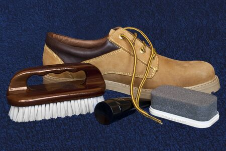 Composition with the boot and things to take care for shoes, isolated on blue background