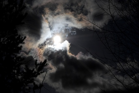 The sun looks out from behind black clouds
